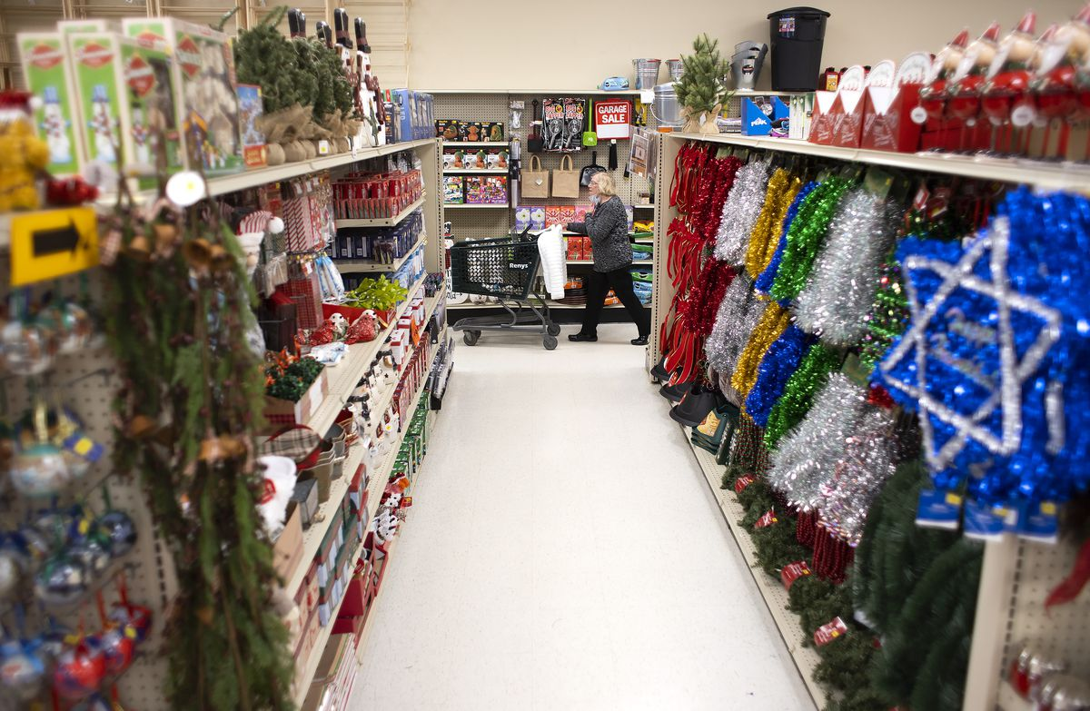 A shopper with a mask rolls her cart down the end of an aisle full of holiday decorations
