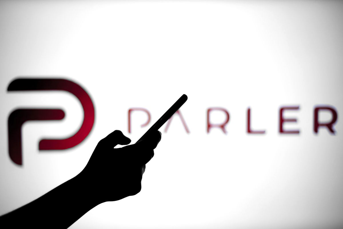In this photo illustration a Parler logo is seen behind a...