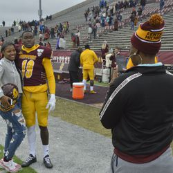 Tyrone Scott poses for pictures with loved ones post-game.