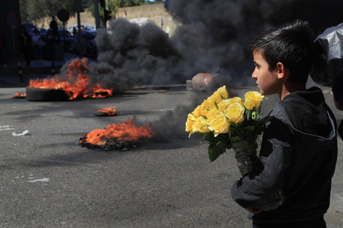 A Syrian boy who sells flowers on the street watches protesters burn tires to block a main road during a protest against the increase in prices of consumer goods and the crash of the local currency, in Beirut, Lebanon, Tuesday, March 16, 2021.