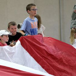 Kids help unfurl a giant American flag at the South Towne Expo Center in Sandy on Wednesday, May 31, 2017. The flag, which measures 78 feet by 125 feet, will fly between the two peaks at Grove Canyon in Pleasant Grove on the morning of July 4th. The organization Follow the Flag believes it will be the largest American flag ever flown.