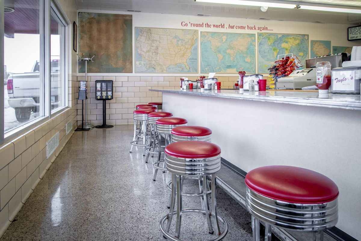 The inside of a historic diner with red leather stools at a counter and an atlas of the world