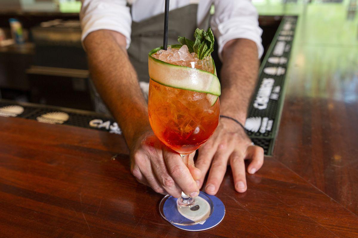Δύο χέρια σπρώχνουν ένα μακρύ κόκκινο ποτό σε ένα τεράστιο ποτήρι κρασί τυλιγμένο σε μια λεπτή φέτα αγγουριού προς τα εμπρός