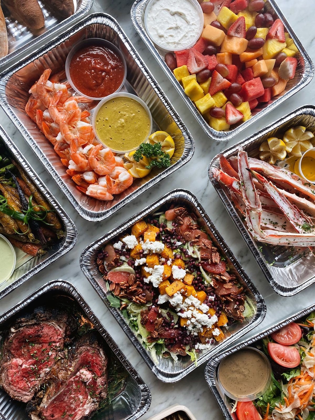 6Smith's Easter take-and-make meals all portioned in aluminum takeout containers. Prime-rib, salad, shrimp cocktail, fruit salad, and crab legs are pictured.