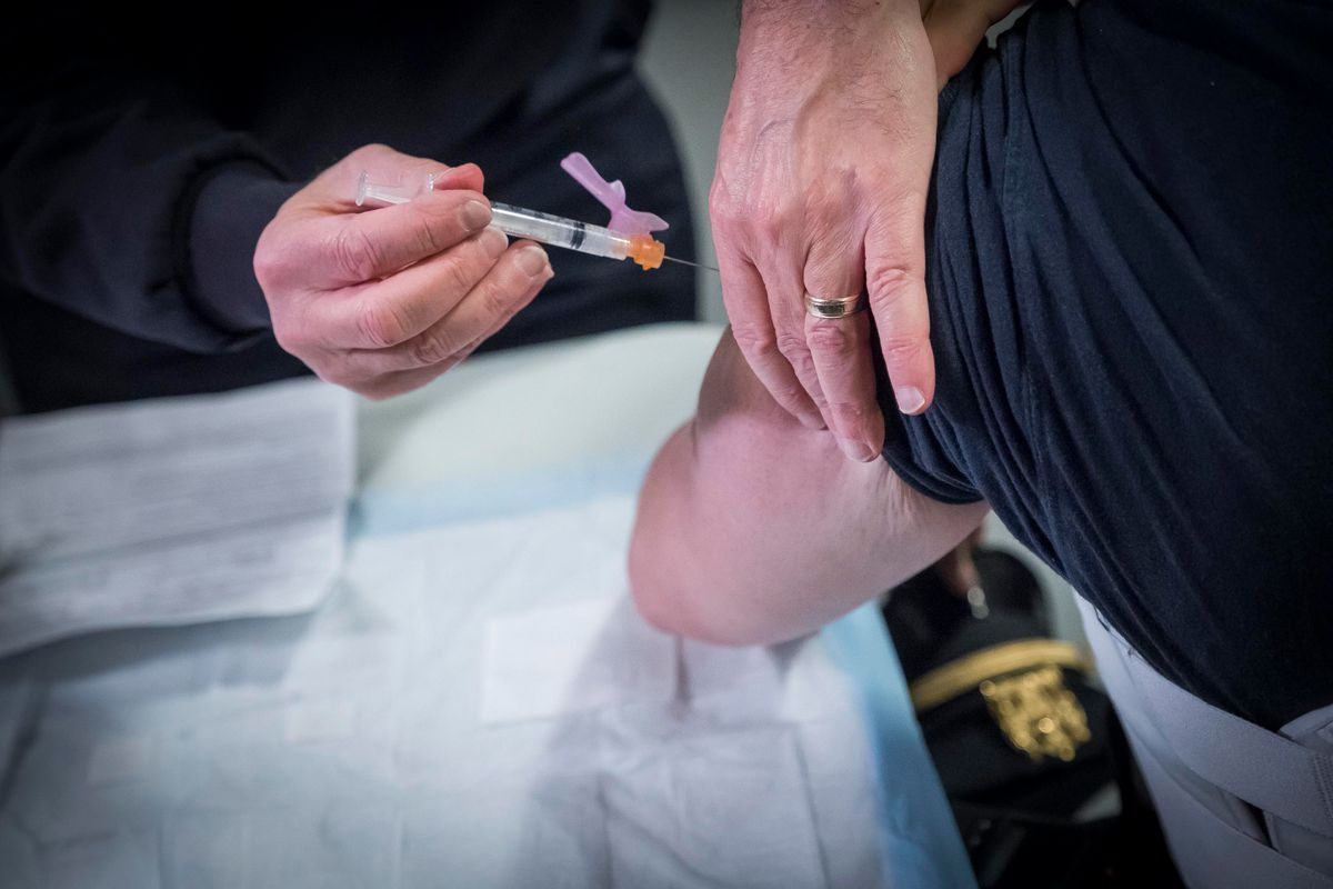 A health care worker in Queens gives a protective shot in the arm, Jan. 11, 2021.