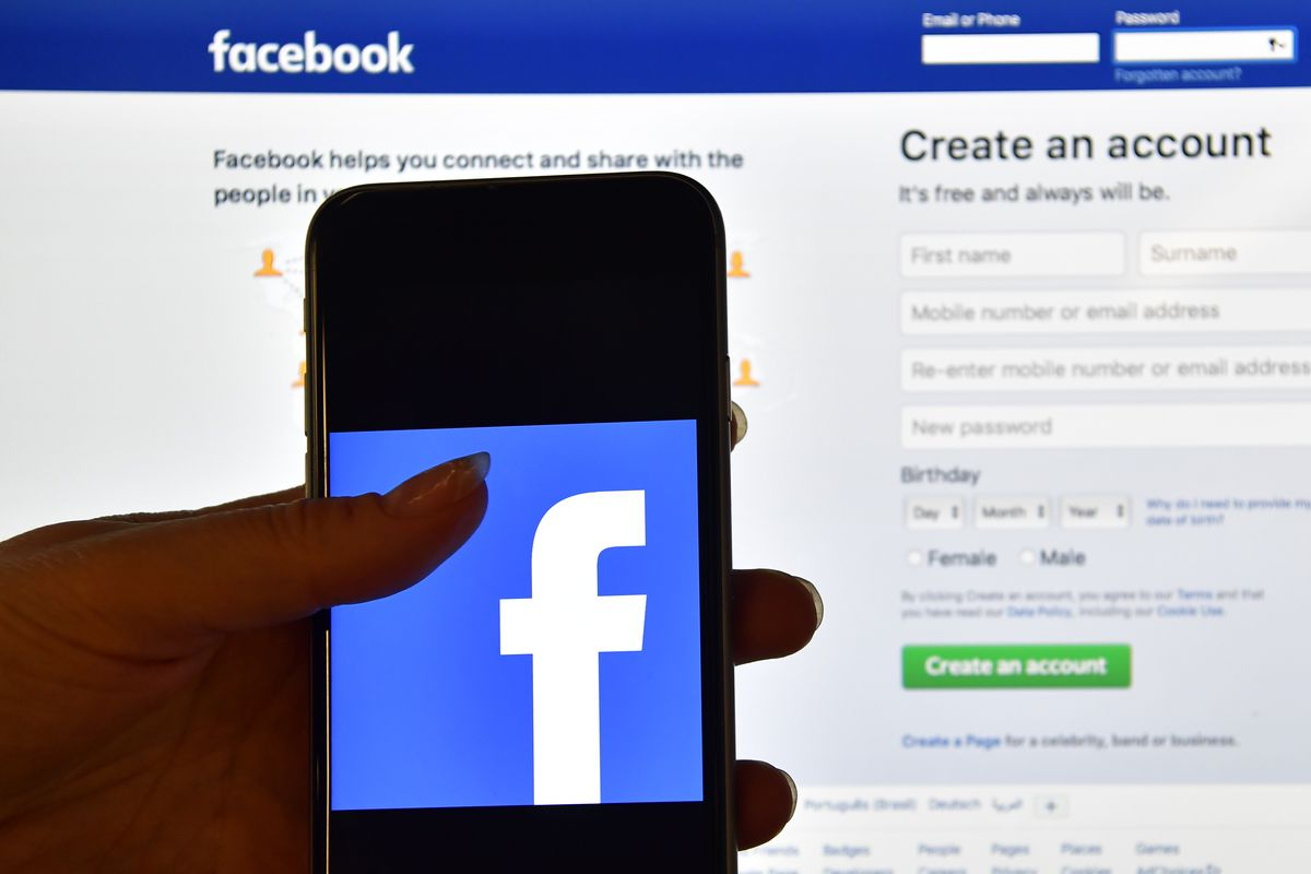 """A cellphone showing the Facebook logo, held in front of a computer screen showing Facebook's """"create an account"""" page."""