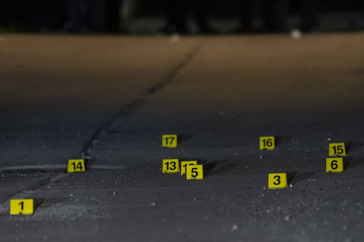 Shell casings and more than 41 evidence markers litter the ground in an alley in the 1600 block of East 87th Place, where six people were shot, one fatally, Saturday night.