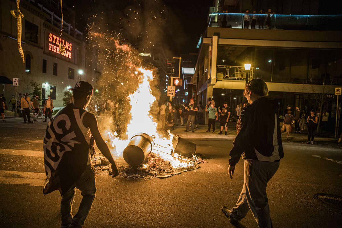 Protesters set a dumpster on fire after a shooting on Thursday, June 3, 2021 in Minneapolis. Crowds vandalized buildings and stole from businesses in Minneapolis' Uptown neighborhood after officials said a man wanted for illegally possessing a gun was fatally shot by authorities.