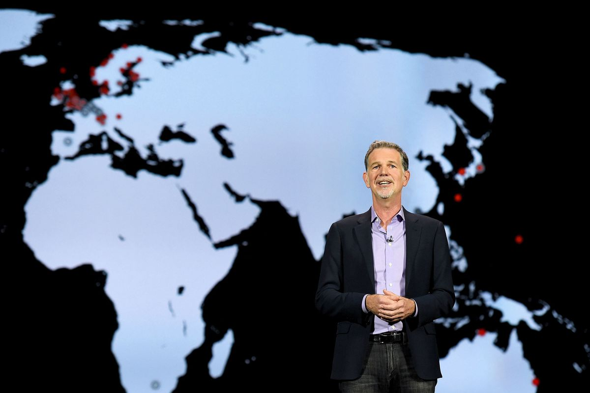 Reed Hastings, CEO of Netflix International stands before a map of the world as he speaks on a stage.