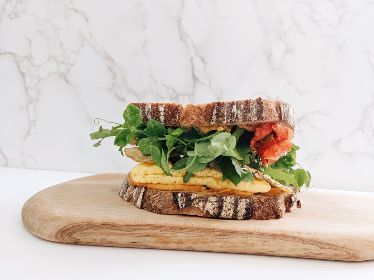 The Cade Stack features the JUST Egg Folded, topped with shakshuka cheese sauce, Rosemary potato chips, greens, lettuce leaf basil, and served on a plant-based country bread from Zingerman's