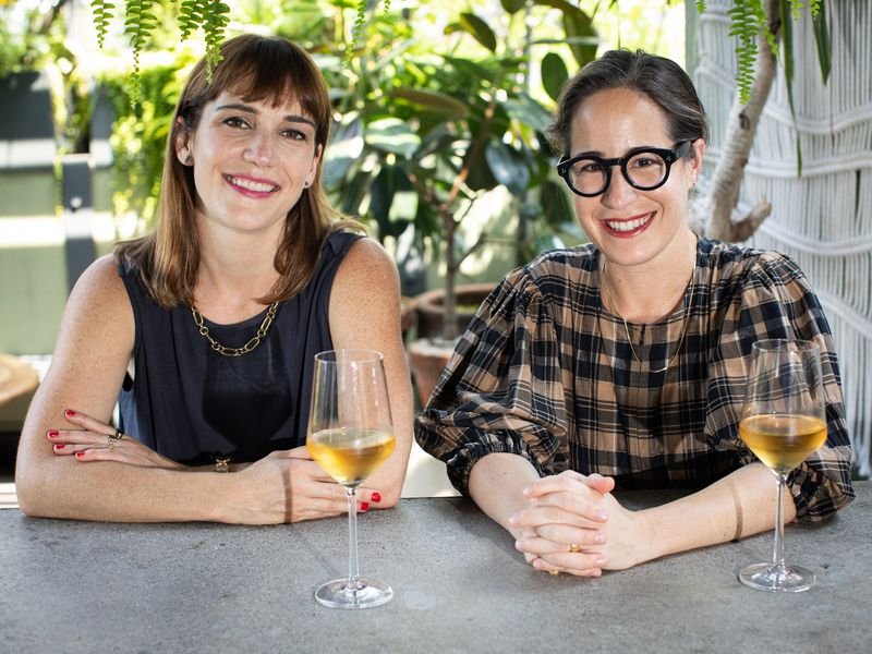 Two smiling white women sitting at an outdoor table with frosty glasses of orange wine, with greenery behind them