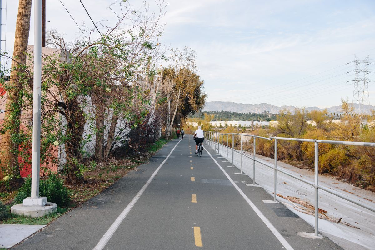 A cyclist rides along an open bike path that abuts a mostly dry river.