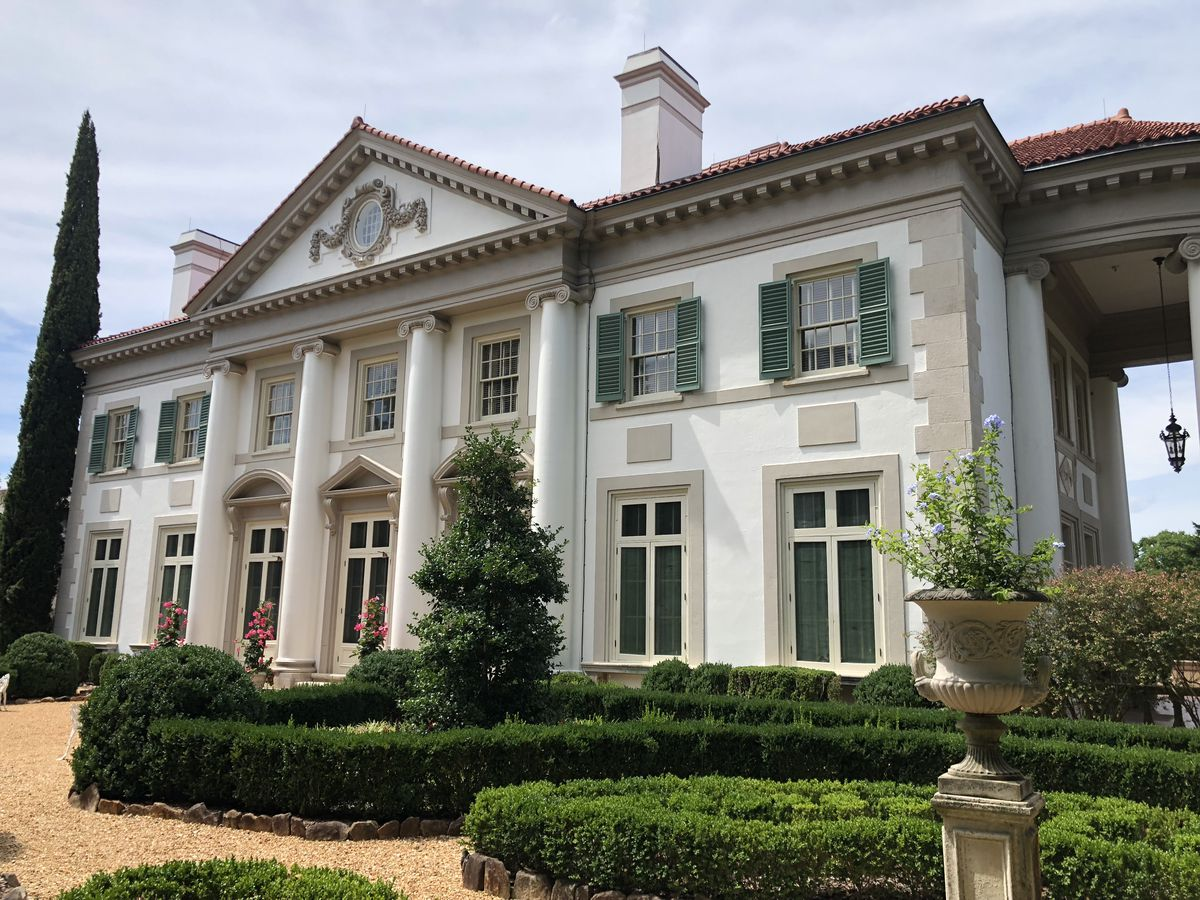 The exterior of Hills and Dales Estate in Atlanta. The facade is white with columns. There is a garden with topiaries in front of the house.