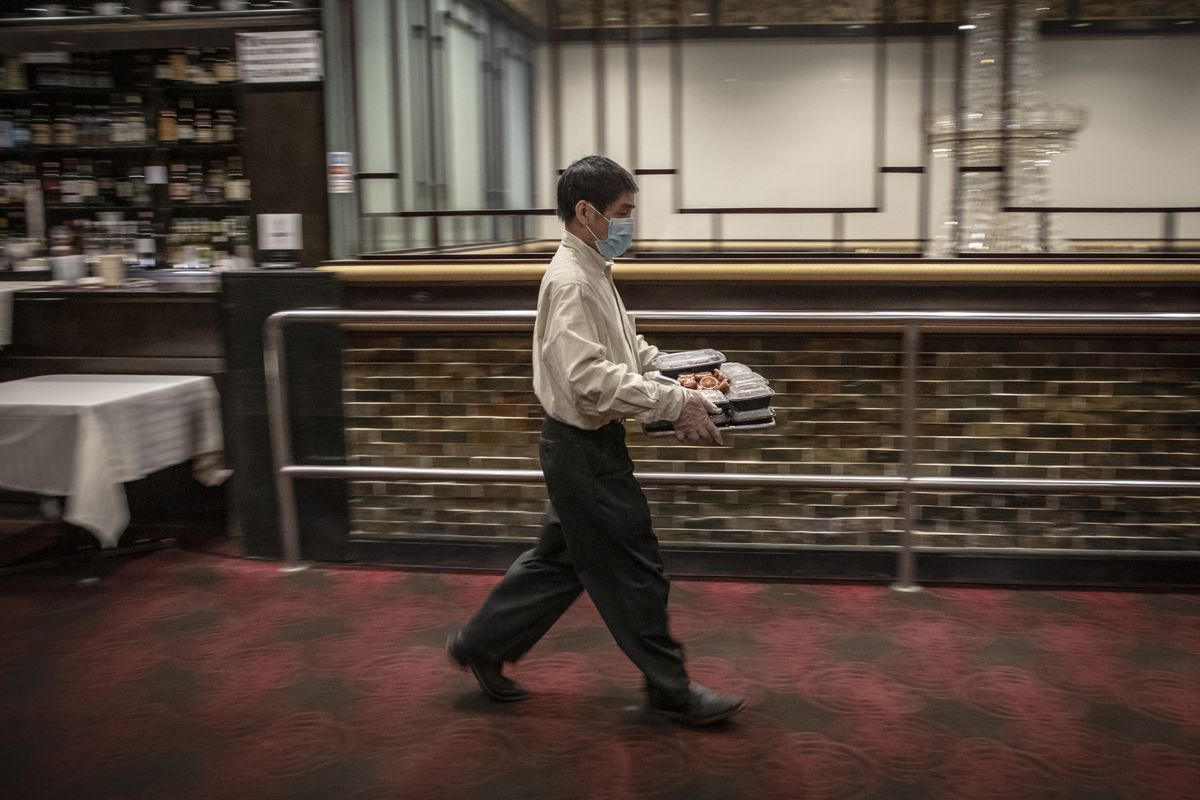 A waiter carries a tray of food
