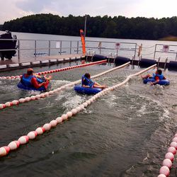 Launching off the bristly slide, riders land in the lake water.