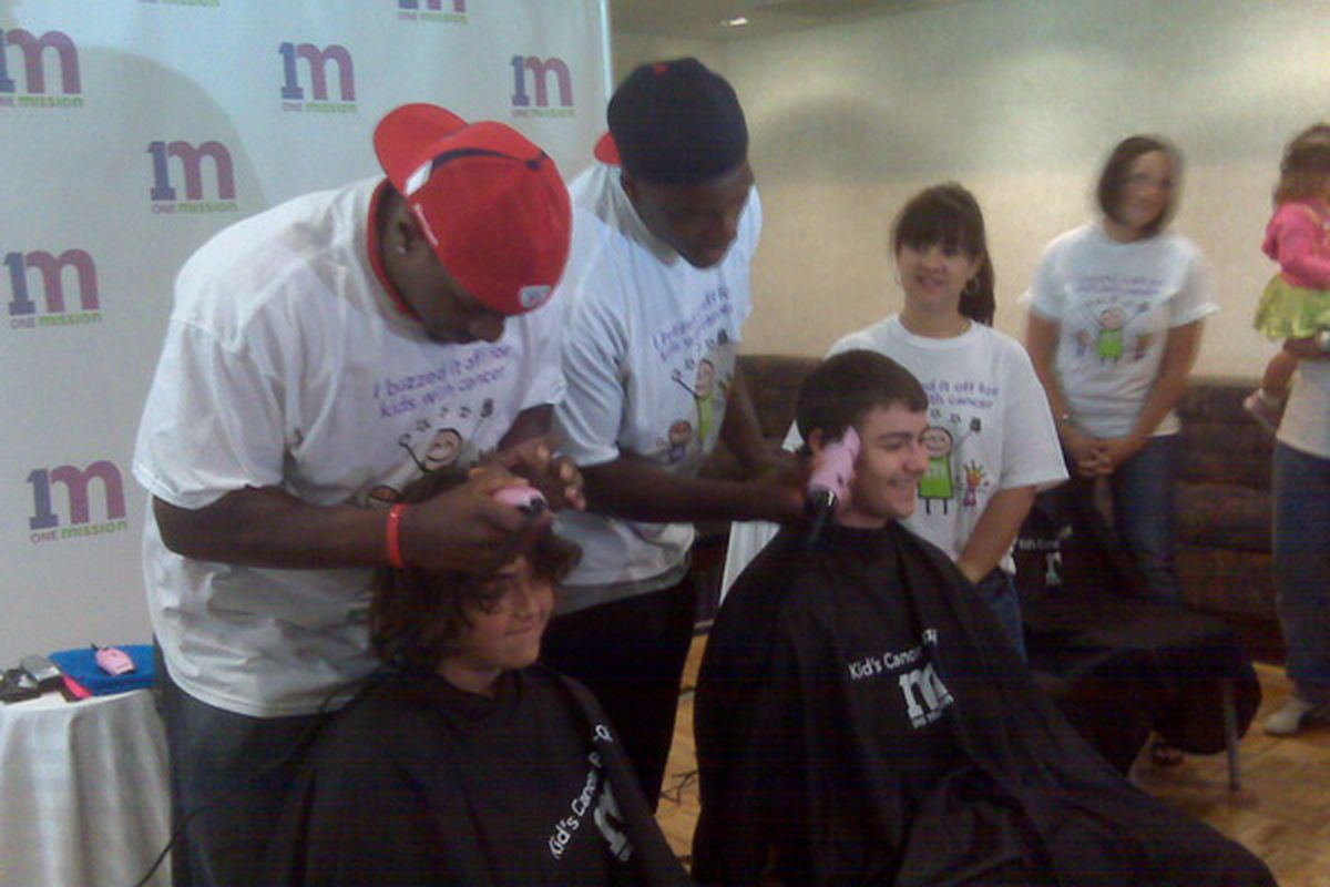 """<em>Linebackers Pierre Woods and Tyrone McKenzie participate in a """"Cancer Buzz-Off"""" charity event</em>."""