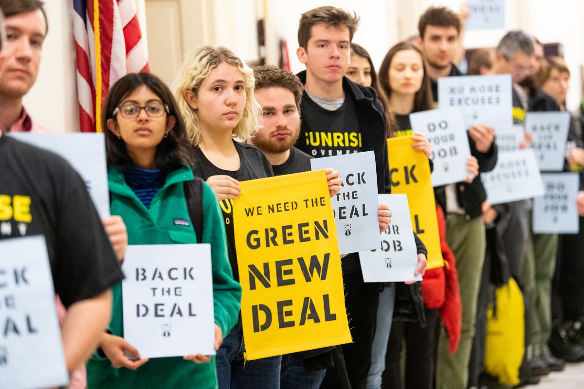 Protesters seen holding placards during the Sunrise Movement protest inside the office of US Representative Nancy Pelosi (D-CA) to advocate that Democrats support the Green New Deal.