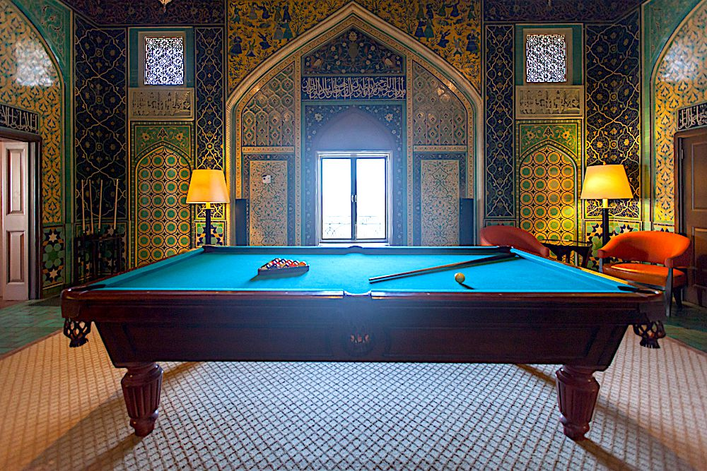 The interior of the Fairmont San Francisco Penthouse. There is a billiard table, chairs, and lamps. The walls have an inlaid design.