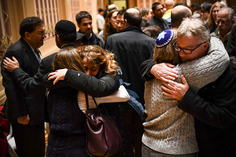 People hug after a vigil to remember the victims of the shooting at the Tree of Life synagogue.