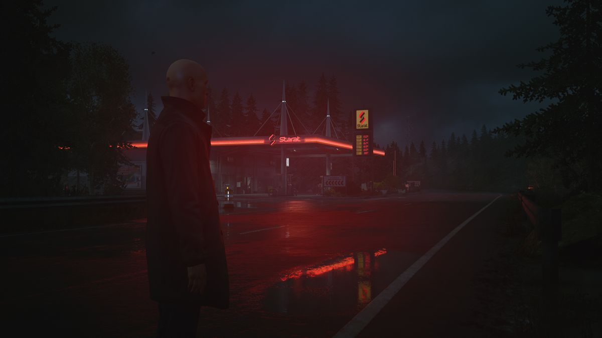 Agent 47 wearing a long coat with his collar popped, standing on a lonely road in a forested area at night with a gas station in the background in Hitman 3