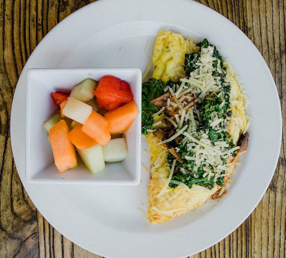 A bowl of fruit next to an omelet with kale on top