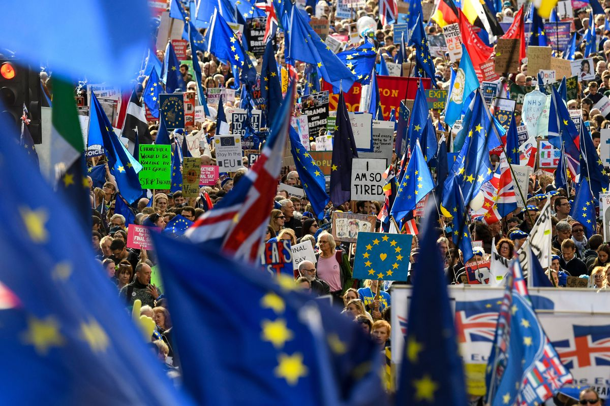 "A sea of EU flags are raised among signs with messages like ""Stay in the EU,"" ""I will always love EU,"" and ""I am so tired."""