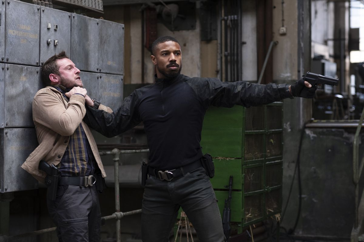 Michael B. Jordan holds a man by his throat while point a pistol off-screen.