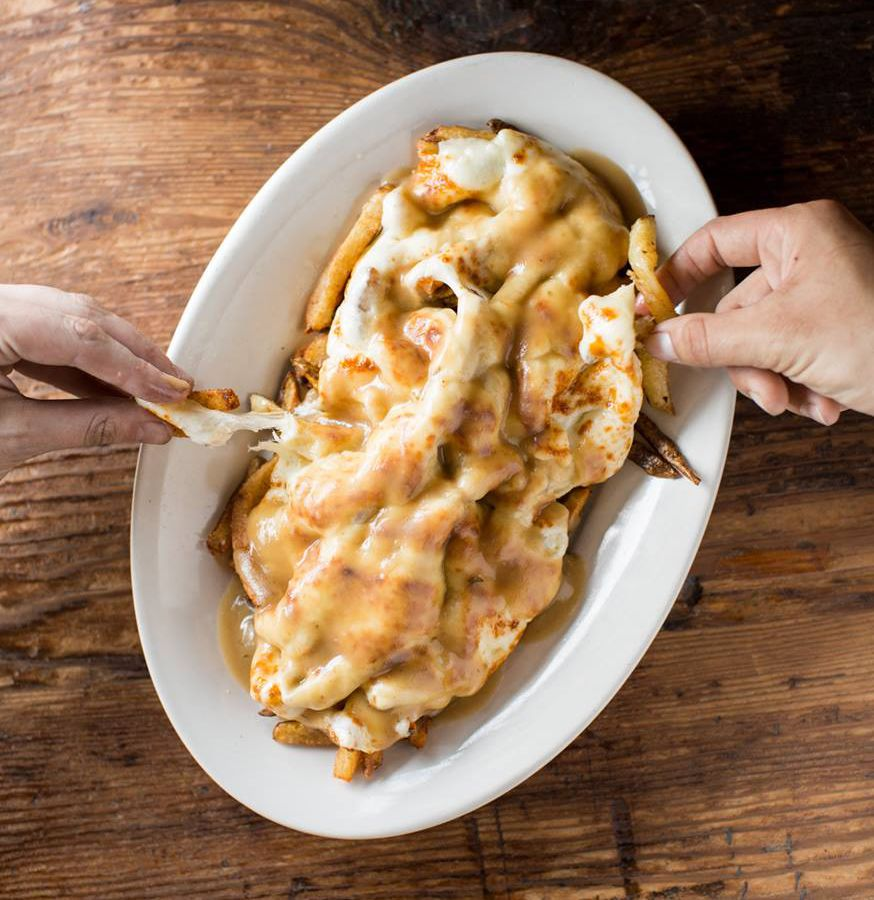 A bowl filled with cheesy poutine