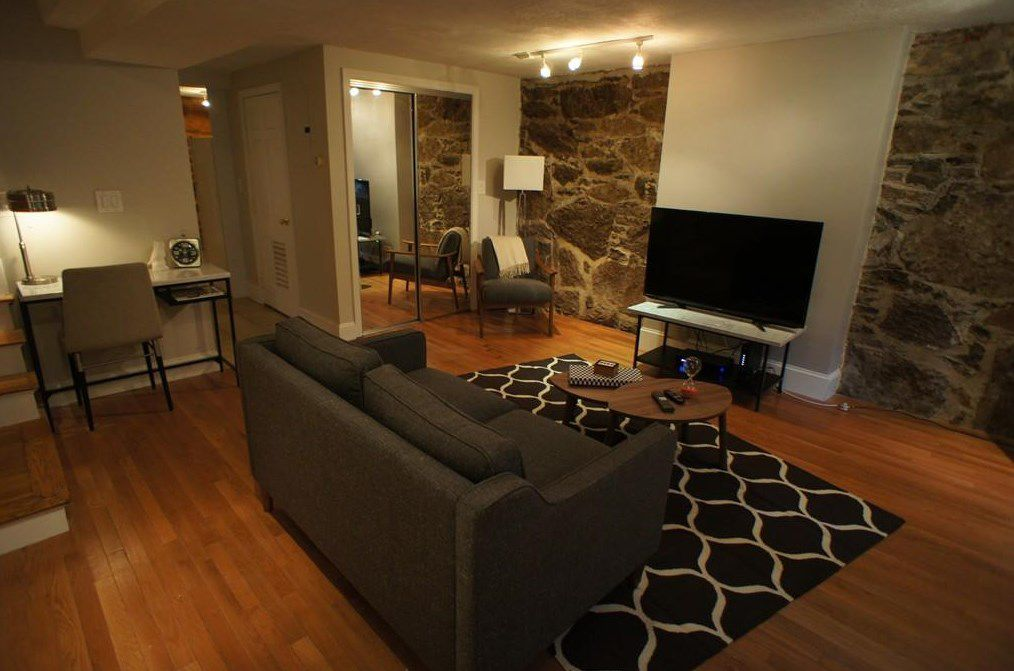 A sizable living room with a couch facing a TV.