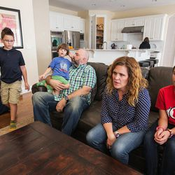 Trey and Heidi Wallis sit with their kids, Bubba, left, Louie, on Trey's lap, Sam, in the kitchen, and Ellie as they talk about why they are fighting to have GAMT screening placed on the national newborn screening list during an interview in their Bluffdale home on Wednesday, Nov. 2, 2016. Louie and Sam have the rare disease guanidinoacetate methyltransferase (GAMT) deficiency.