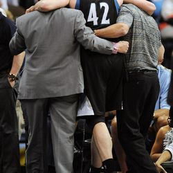 Trainers help Minnesota Timberwolves power forward Kevin Love (42) off the court after he was hurt in a collision in the first quarter of an NBA basketball game against the Denver Nuggets in Denver, Wednesday, April 11, 2012.
