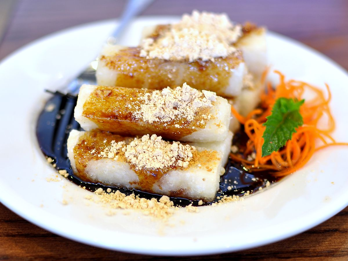 Rice cakes in a sugary syrup on a plate.
