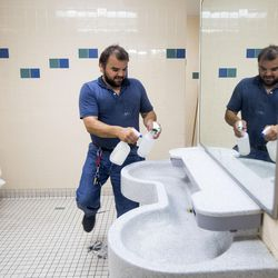 Cody Duran, an employee of Catholic Community Services, cleans the men's restroom at the Weigand Homeless Resource Center in Salt Lake City on Thursday, June 29, 2017. The restrooms are cleaned every day and the center upholds the policy that if the staff wouldn't use the restrooms then they aren't clean enough.