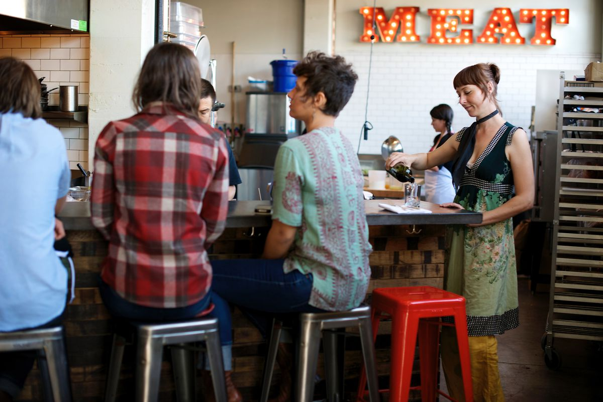 Diners sit around the bar at Olympia Provisions' Southeast Portland location
