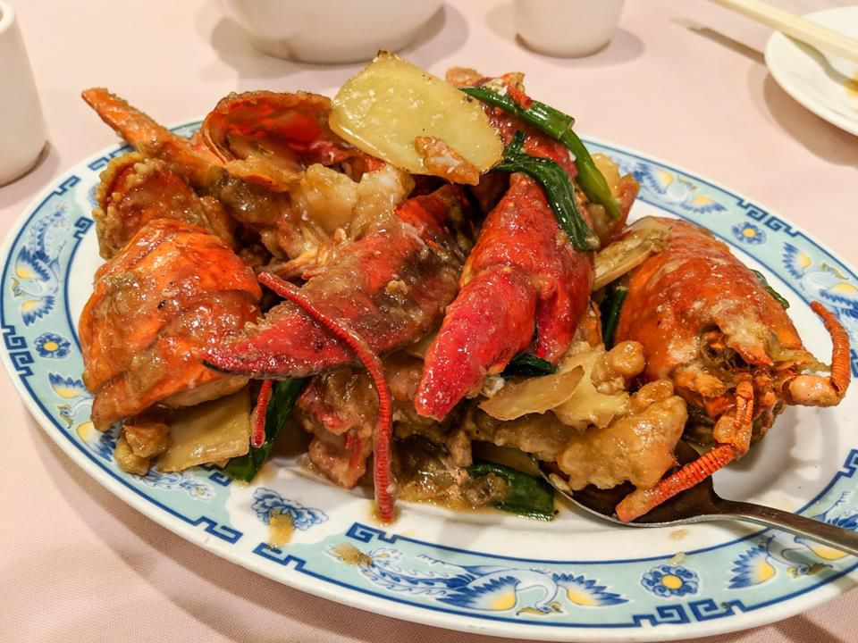 A plate with a blue border embellished by birds holds a portion of lobster with scallions and ginger