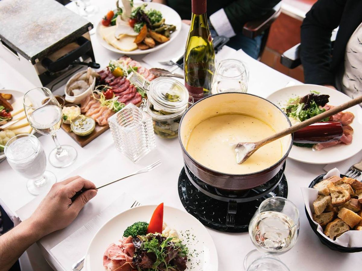 A fondue pot in the middle of a table.