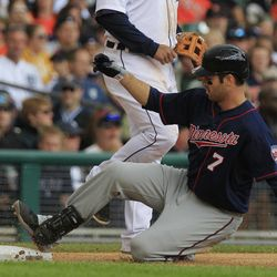 Minnesota Twins' Joe Mauer (7) safely slides into third while scoring two runs during the eighth inning of a baseball game against the Detroit Tigers at Comerica Park in Detroit, Sunday, Sept. 23, 2012.
