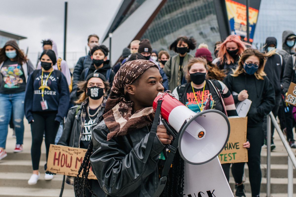 A young woman wearing a black jacket and brown headdress speaks through a red and white bullhorn microphone. There are several students holding signs or standing in solidarity behind her.