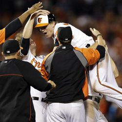 Baltimore Orioles' Nate McLouth, center, celebrates with teammates after Manny Machado scored a run on McLouth's single in the ninth inning of a baseball game against the Tampa Bay Rays in Baltimore, Wednesday, Sept. 12, 2012. Baltimore won 3-2.