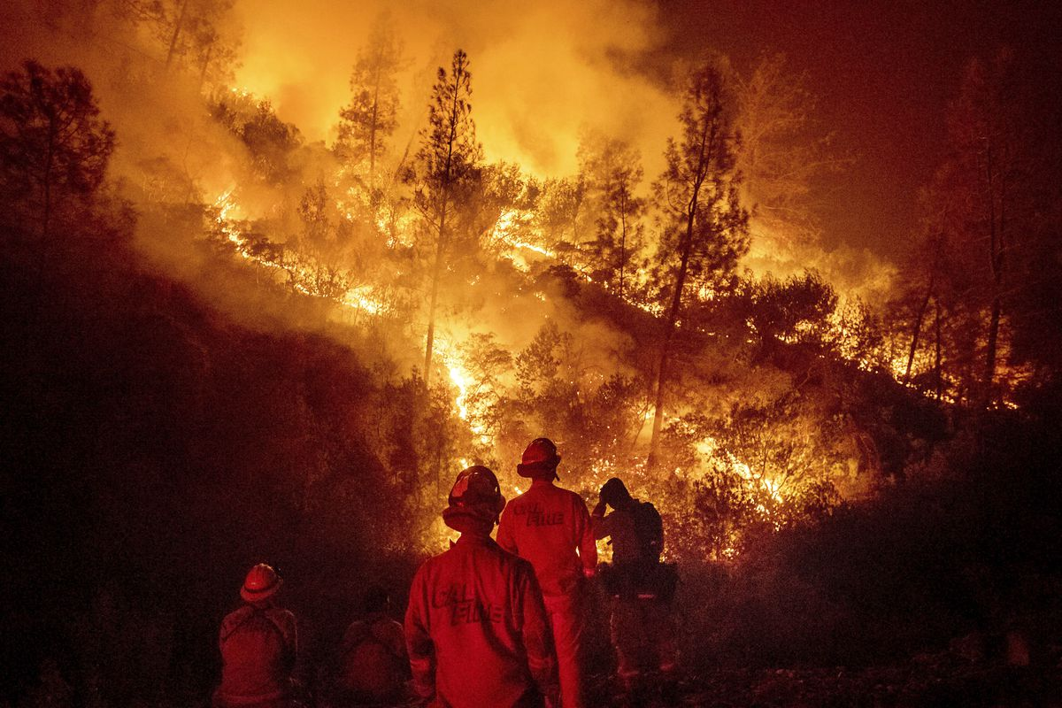 FILE - In this Aug. 7, 2018 file photo, firefighters monitor a backfire while battling the Ranch Fire, part of the Mendocino Complex Fire near Ladoga, Calif. A nationwide telecommunications company that slowed internet service to firefighters as they batt