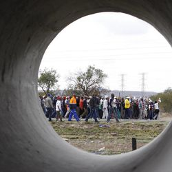 Striking platinum miners take part in a march to the Rustenburg, South Africa, police station, Sunday, Sept. 16, 2012 to protest the heavy handed way the police are cracking down on strikers who have been off work since early last month. The march was declared illegal by the police, who prevented the protesters from entering the town, and the strikers dispersed peacefully.