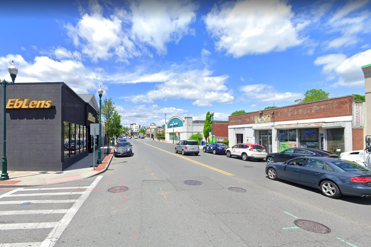 A street lined with storefronts and cars in New Rochelle, New York