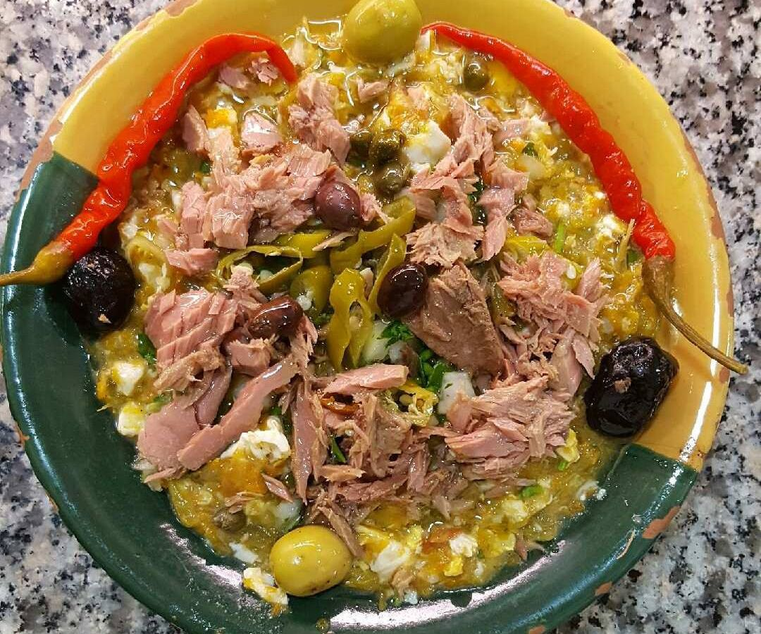From above, a multicolored dish filled with eggy stew of vegetables, olives, shredded meat, and peppers