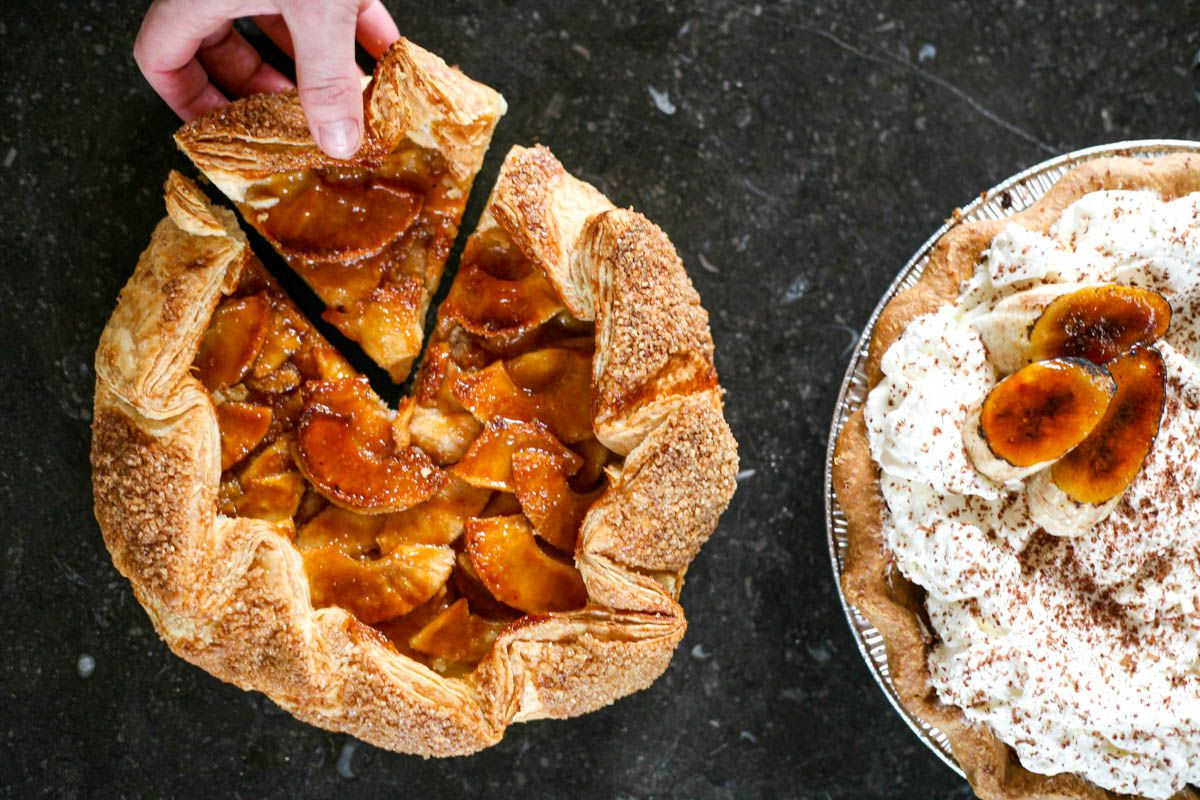 A rustic apple pie with a slice being taken out and a whipped cream-covered pie.