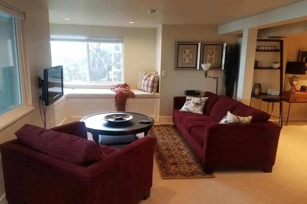 A living room features maroon furniture and a window bench in the back