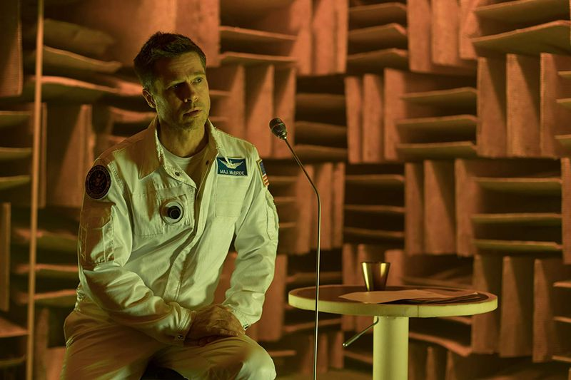 "Brad Pitt sits onstage in front of a microphone in the movie ""Ad Astra."""