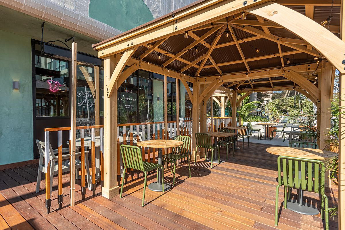 Distanced seating and lots of wood under a new gazebo at a restaurant.