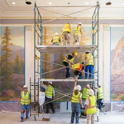 A team of muralists install a large section of canvas in one of the instruction rooms of the Mesa Arizona Temple in July 2020. They use an innovative process that allows precise placement of the large swaths of material.