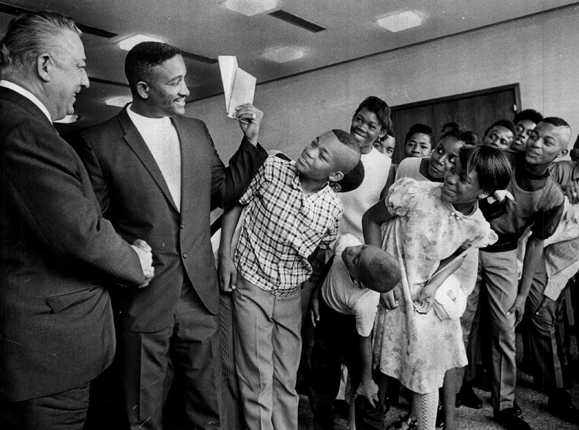 Bailey K. Howard (left), the president of Field Enterprises Inc., shakes hands with Sidney Bennett, presenting him with two $1,000 checks for rescuing Sun-Times photographer Mel Larson from a street beating in 1968.