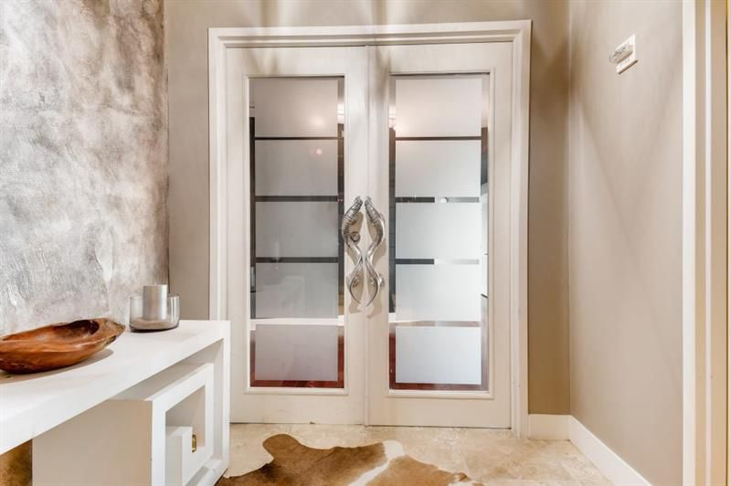An entry with two huge doors and big silver handles in a condo.